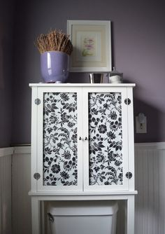 Update or create a bathroom storage cabinet by painting and lining a cabinet face with pretty fabric for a fresh look.