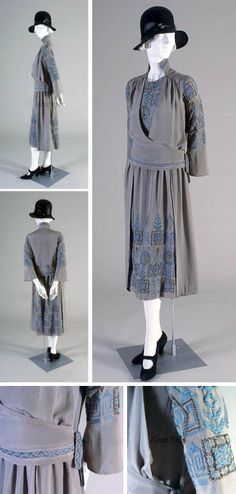 """Dress, Elizabeth Bertch, Youngstown, OH, ca. 1920s. Gray silk crepe embroidered with geometric pattern in blue thread, tarnished silver floss, & seed beads. Round front neck, stand collar with embroidered back. Unfitted bodice with embroidered panel on front & left shoulder snap closure. Attached vest-like overwrap. Embroidered hip band & loop with snap closure at left hip; lightly gathered skirt with embroidered """"floating panels"""" lined with chiffon. Kent State Univ. Museum"""
