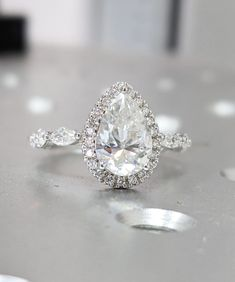 This off-center, pear-shaped moissanite engagement ring is in keeping with today's trends, while still maintaining a timeless elegance in the design. #vintagerings #vintageengagementrings #engagementrings #southernliving