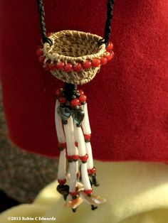 I use raffia alot and for the basket necklace I also used waxed black linen string; dentalium shells(Native American money in some regions); red/white heart trade beads; abalone carved hearts; carved shell birds. Woven by Robin Carneen Edwards