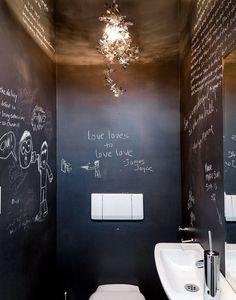 Tegenwoordig hebben mensen vaak een krijtbord in huis. In de keuken, in de kinderkamer, in de hal, maar ook in het toilet zou je iets met krijtbord kunnen doen. In onderstaand toilet zijn ze zelfs nog een stapje verder gegaan. Ze hebben namelijk alle muren bekleed met krijtbord muurstickers! Het toilet is hierdoor nogal donker, maar het witte hangtoilet, de spoelknop en het fonteintje zorgen voor het contrast. En de gouden hanglamp is natuurlijk ook prachtig!