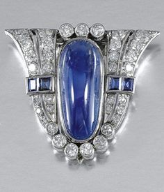 AN ART DECO SAPPHIRE AND DIAMOND CLIP BROOCH, 1930. The shield-shaped plaque, set to the centre with an oval cabochon sapphire, to tapered shoulders millegrain-set with step-cut sapphires, brilliant- and single- cut diamonds, fitted case.