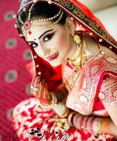 bride in a lush red bridal katan saree.
