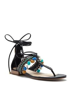 Step into the season with this fun and festive flat sandal by Vince Camuto. Made of leather with decorative pom poms and a sleek ankle tie that lend sweet and sassy flair to any ensemble.