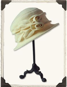 CREAM ROSES HAT AND HATBOX Hand-turned blooms and leaves upon a soft wool brim will ward off winter's chill.
