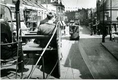 https://flic.kr/p/kMPHQw | 1937 Bristol Tram Car 7 on East Street, Bedminster BS3 | Brillant view from the top deck of a Bristol tram car on route through Bedminster. When it rained on the top of the tram you had to turn the seat over to the dry side. Note: on the left 82. E. Luton & Son, bakers, 78. Halfords cycle shop, 78a. Rialto, ladies hair dressing salon, 76. Fleming Reid & Co. Ltd, hosiery & wool shop, 74. Mitchell, wine & spirt dealer. 74a. George Loxton, dentist, 64-6