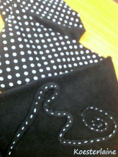 Detail Abrazo (gevoerde sjaal met zakken)  De applicatie is van een lint van fleece met wit borduurgaren. Het stelt een golf voor. Het uiteinde van het lint eindigt in de zak en er zijn witte kraaltjes aan het einde bevestigd.