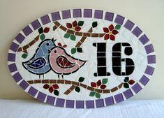 Numero residencial em mosaico, tamanho oval médio (38x25). Cliente pode escolher cor da borda e do número. O mosaico é realizado em cima de um piso de ceramica e deverá ser fixado na parede com argamassa. Ou poderá ser feito 2 furos para parafusar na parede a pedido do cliente.