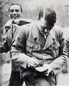 Goebbels photo bombs Hitler. Date unknown