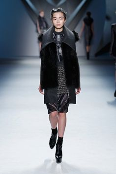 Charcoal melton sleeveless coat with raccoon vest and structural collar over black vault print silk chiffon sleeveless dress with stand melton collar and crystal mesh apron.