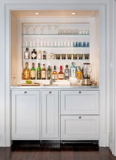 Fabulous recessed wet bar with white base cabinetry.  Hidden: a pair of dishwasher drawers. The bar also features a small bar sink with gooseneck faucet. The cabinets pair with brushed nickel hardware and marble countertops. Above the cabinetry, recessed glass shelves hold liquor and glassware. Dark hardwood floors contrast the white paneled walls. Recessed lighting adds ambiance to the bar area.