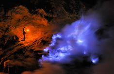 A sulfur miner stands inside the crater of the Kawah Ijen volcano at night, holding a torch, looking towards a flow of liquid sulfur which has caught fire and burns with an eerie blue flame. (© Olivier Grunewald)