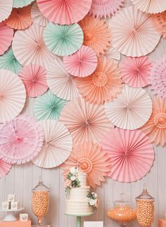 Top 10 Wedding Backdrop Ideas - Use Plenty of Rosettes: Paper rosettes are another great go-to decoration, especially if you're inspired by color and texture. Mix and match different rosettes to create a wall display that really comes to life! Add in a few paper pom-poms for more volume. Use a single color to highlight your venue or color scheme, or try an ombre arrangement to add subtle variation. Photo from The Sweetest Occasion // Charlie & Juliet.