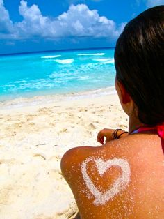 an outline of a heart made with sand on a girls back... with a beautiful view of the ocean in front of her