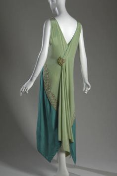 1928.Dress of light green silk charmeuse with blue green side panels. V-shaped neckline front and back; sleeveless; hem falls to knee in front, and to the ankles in back. Pearl and metallic thread embroidery form a wing pattern across chest, and an uneven scallop pattern on the skirt. Back features a fan-shaped brooch made of pearls and glass beads.