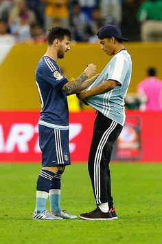 #COPA2016 Lionel Messi of Argentina autographs the shirt of a fan who ran onto the field prior to the start of the second half during a 2016 Copa America...