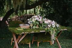 Moss covered table and chairs with cascading centerpiece