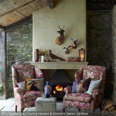Tierdeko, Feuer und Mauerwand: Das Kaminzimmer des Landhauses ist eng mit der Natur verzahnt. Rehmotive und unterschiedliche Vogeldeko zusammen mit den geblümten …