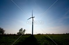 silhouette view of a wind mill farm. - Silhouette view of a wind mill farm against blue sky in the background.