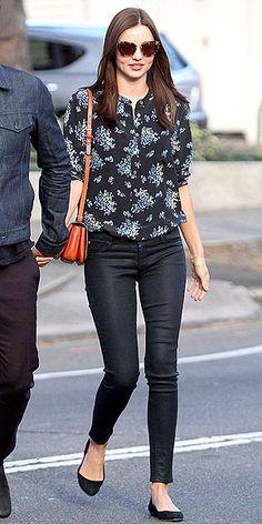 Miranda Kerr blusa floreada en tono negro; pantalon negro, ballerina negra
