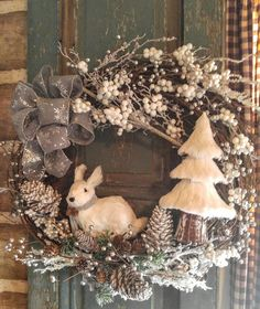 Christmas Winter Wonderland Bunny Wreath. Adorable woodland white bunny surrounded with an abundance of white snow & pearl berries, silver berries, shimmering twigs, snowy & rustic pinecones, large silver pinecones, whimsical white tree, glistening sliver stems and a silver snowflake bow. A beautiful Running Rustic original design. Approx.. 20x20