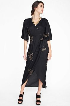 This lightweight maxi wrap dress features an allover gold cherry blossom print, plunging neckline, an embellished sash to cinch around your waist, and a tulip hemline that falls delicately around the