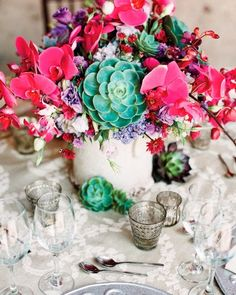 Glazed ceramic vases bursting with lisianthus, native succulents, fuchsia orchids, and hydrangeas shared the table with mercury glass votives.