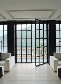 A grid of black steel doors, leading to waterfront balcony | Anouska Temple Design