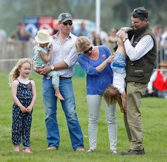 (L-R) Savannah Phillips, Isla Phillips, Peter Phillips, Autumn Phillips look on as Vice Admiral Sir Timothy Laurence holds granddaughter Mia Tindall upside down as they attend the Badminton Horse Trials on May 7, 2016 in Badminton, England.