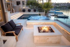 A fire pit surrounded by seating creates a cozy spot to relax beside this breathtaking lakefront view. The infinity-edge pool and hot tub are surrounded by square glass tiles, which draw the eye and create a colorful focal point in the neutral space.