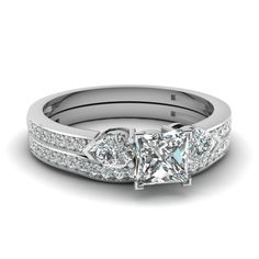 This magnificent wedding ring set features an #engagementring with prong set center stone which is flanked by two prong set pear shaped #diamonds. Further augmenting the artistic look of the #ring are pave set round cut diamonds on either sides of the center stone. http://jangmijewelry.com/