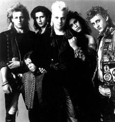 Os Garotos Perdidos. Personagens com pose de banda de rock. Jovens vampiros assombram uma pacata cidade litorânea da década de 1980.