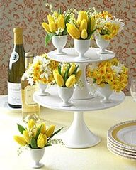 Here's another way to use the white serving stands,little egg holders hold the flowers to create a pretty centerpiece.