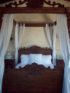 Carved wooden four poster canopy bed
