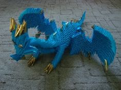 How to make 3d origami dragon  Pieces needed: ~1000blue and 36 golden(or yellow)  How to fold pieces: http://www.youtube.com/watch?v=1BzvCU40fDU