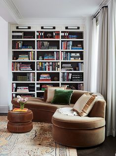The designers had the back of these built-in bookshelves painted black—a simple trick that helps visually ground the room and allows the objects on display to really pop.