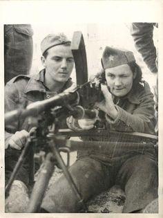 1944- British soldier teaches a female Yugoslavian partisan how to use a Bren gun at base in Malta.
