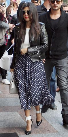Kourtney Kardashian was spotted hitting the shops in Paris in a polka dot print pleated Asos midi skirt, complete with a crisp white crop top, a black moto jacket, a ladylike top-handle bag, and two-toned ankle-cuff pumps.