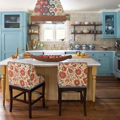 A mustard yellow plank island, white quartz countertop, a multi-colored range hood and chic chairs of the same pattern, along with white and gray mosaic backsplash present such a perfect combination with muted blue country style cabinets.  Kitchen Design by Andrea Schumacher Interiors   #countrykitchendecor #kitchendesign #countrykitchenstyle #kitchen #interiordesign #countrykitchendesign #kitchendecor #homedecor #interior #kitchenremodel #home #homedesign #architecture #kitcheninspo