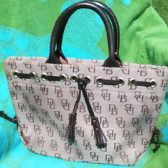 Authentic Dooney & Bourke tote Beautiful canvas and dark brown leather Tassel purse ! It is in great condition. Inside and out are clean with no stains, tears or damages! Medium tote purse. Dooney & Bourke Bags Totes