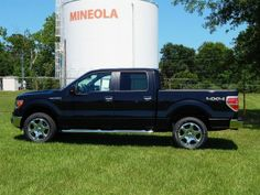 2014 Ford F150 XLT SuperCrew 4X4 in Tuxedo Black. This F150 looks good on the grass in front of the #MineolaTX water tank.