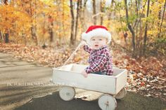 8 month old baby boy in an antique wagon with a Santa hat for Christmas Pictures