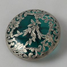 Antique extra large button of glass set in pierced metal backing and covered with metal leaves and flowers. Silver colored metal but content is unknown. But it sure is pretty!