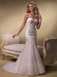 """Designer: Maggie Sottero """"Everett""""    Description: Swarovski crystals sparkle in gorgeous lace motifs featured in this elegant slim A-line gown finished with corset back closure. A stunning statement in a simple design.    $1089.00"""