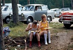 Ruegen. 1974. Vacationers in the woods on the shore of the Baltic Sea have lunch in a parking lot in front of their Trabant and Skoda cars.