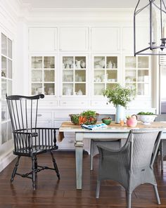 """A warm, community-oriented lifestyle was top of mind when Blazona designed her home: The 20-by-30-foot """"dream kitchen"""" has a farmhouse table that seats 12. In this photo: Blazona's kitchen built-ins hold all her ironstone and glassware. The Windsor chair is by Ethan Allen; the wicker seats are Janus et Cie. White Dove by Benjamin Moore covers the walls.   - CountryLiving.com"""
