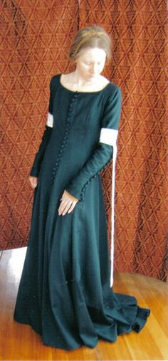A 8-panel wool gabardine dress of the year 1370, designed from several sources of information including the Moy Bog gown, pieces dug up in London and the Greenland finds. It has 53 handmade ball buttons, and hand stitched button holes faced in silk.