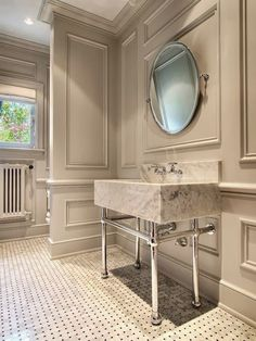 This bathroom makes an elegant statement with gray decorative wall moldings, oval pivot mirror, marble slab washstand, marble basketweave tile floor. Bathroom Baseboard, Baseboard Trim, Wainscoting, Bathroom Moulding, Home Interior, Bathroom Interior, Interior Design, Bad Inspiration, Bathroom Inspiration