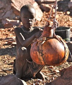 Africa | A little Himba boy sitting next to the kitchen.  The gourd more than likely contains water.  Epupa, Namibia | © gvst via flickr