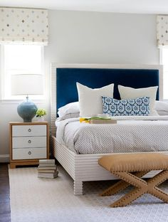 Chic bedroom features a white bed accented with a blue velvet headboard dressed in blue and gray bedding next to a two tone nightstand, Bungalow 5 Berkeley 3 Drawer Side Table, and a blue lamp alongside a burlap x stool with brass nailhead trim.